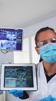 Patiënt pov in tandartspraktijk die de behandeling van tandholte bespreekt, tandarts die op digitale röntgenfoto wijst met behulp van tablet. team van artsen die werkzaam zijn in een moderne stomatologische kliniek, die radiografie tand uitleggen