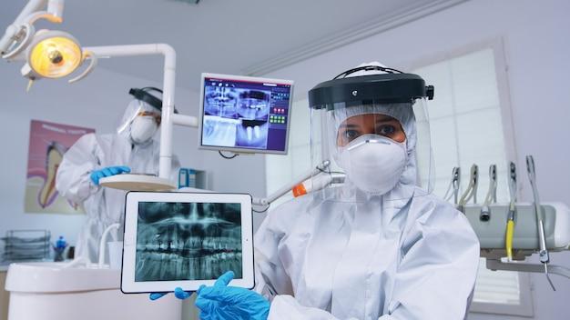 Patiënt pov in tandartspraktijk met nieuwe normale behandeling van tandholte, tandarts wijzend op digitale röntgenfoto met tablet. stomatologie die beschermend hazmat-pak draagt tegen coroanvirus