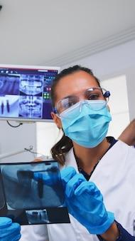 Patiënt pov in tandartspraktijk planning operatie stappen van tanden holte, tandarts wijzend op röntgenbeeld. stomatologie arts met beschermend masker en handschoenen, werkzaam in moderne stomatologische kliniek