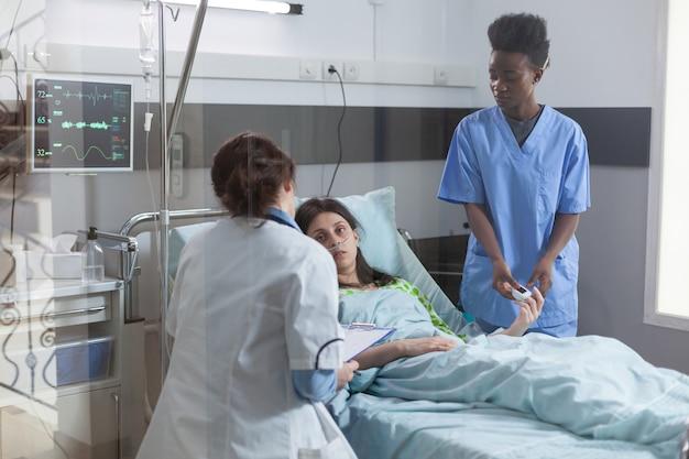 Patiënt rust in bed tijdens herstelconsult terwijl medisch team zieke vrouw bewaakt