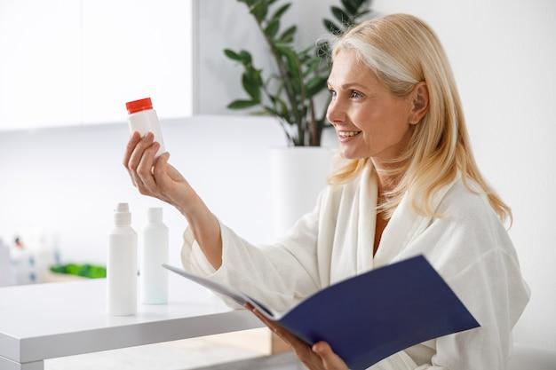 Patiënt senior blonde vrouw stond in de buurt van de receptie en houdt een brochure met schoonheidsbehandelingen.