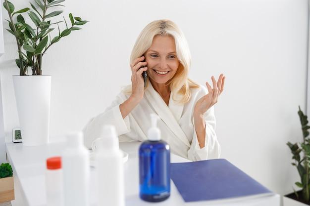 Patiënt senior blonde vrouw stond in de buurt van de receptie, praten over de telefoon met een brochure en schoonheidsbehandelingen op tafel.