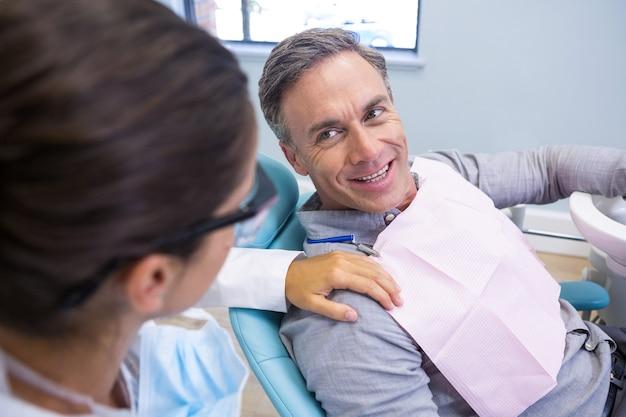 Patiënt tandarts kijken zittend op een stoel in de kliniek