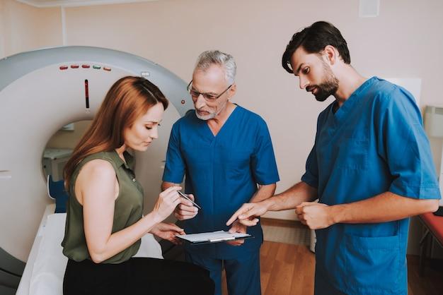 Patiënt tekent papieren overeenkomst voor ct-onderzoek.