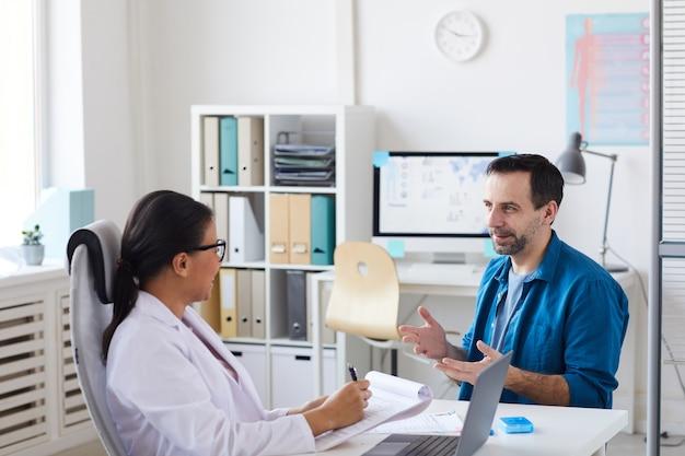 Patiënt zit en gebaart bij de dokter, hij praat met zijn dokter tijdens zijn bezoek
