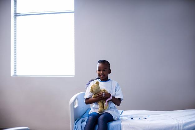 Patiënt zittend op het bed met teddybeer in het ziekenhuis