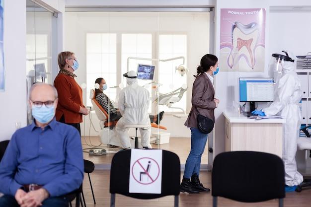 Patiënten met een beschermingsmasker wachten in de stomatologie-receptie met een nieuw normaal, personeel dat een pbm-pak draagt