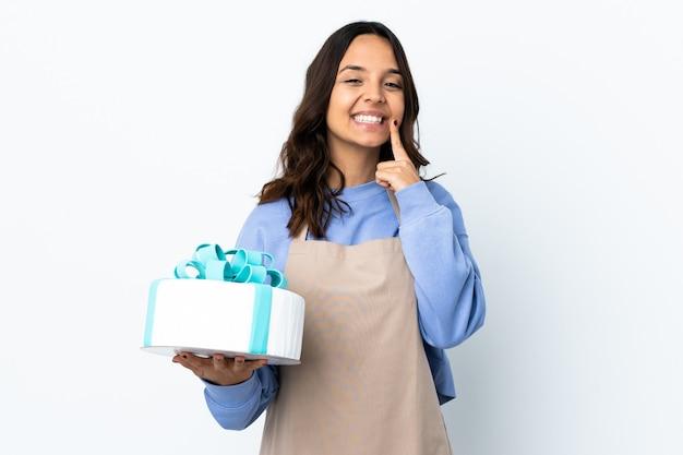 Patissier die een grote cake over geïsoleerde witte achtergrond houdt die met een gelukkige en prettige uitdrukking glimlacht