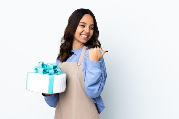 Patissier die een grote geïsoleerde cake houdt die naar de kant wijst om een product te presenteren
