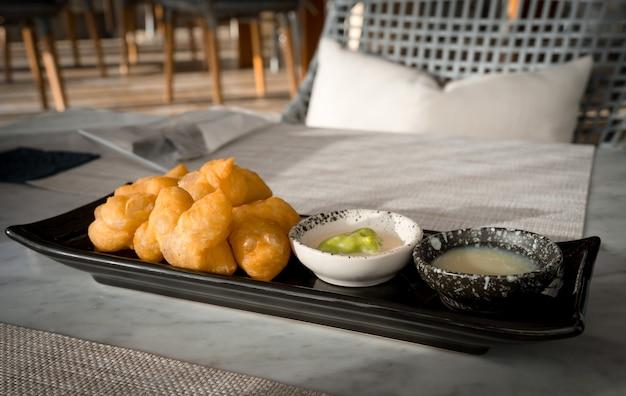 Patonggo of gefrituurde deegsticks op zwarte schotel met pandan en zoete condensmelk die 's ochtends op tafel dompelen, thais ontbijt