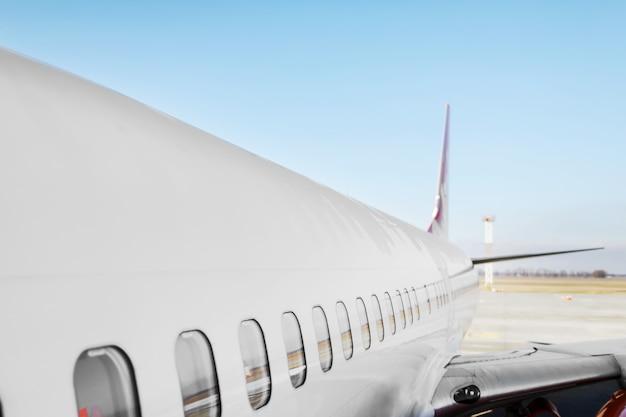 Patrijspoort voor vliegtuigen - zijruit airplain. het witte zware vliegtuig van de passagiersstraalmotor op baan bij luchthaven tegen blauw het vervoersthema van de hemelluchtvaart