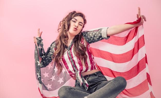 Patriottisch meisje met de vlag van amerika op een gekleurde muur