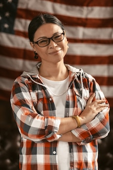 Patriottische amerikaanse glimlach met haar armen gekruist met amerikaanse vlag