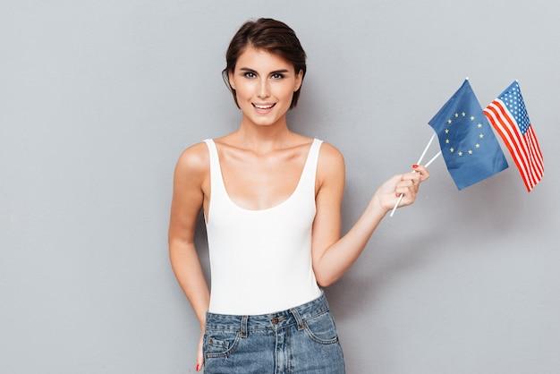 Patriottische gelukkige vrouw met europese en usa vlaggen over grijze achtergrond