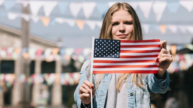 Patriottische vrouw die de vlag van de vs toont bij festival