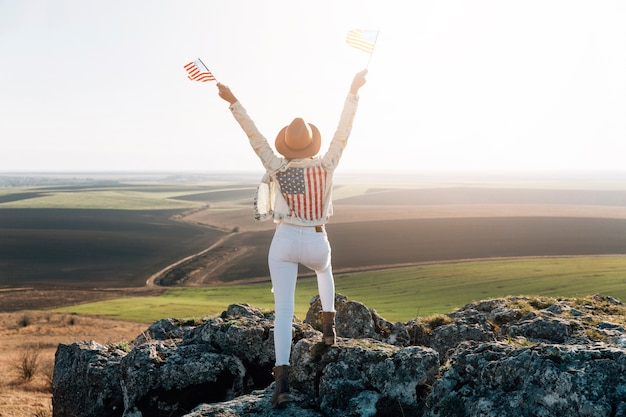 Patriottische vrouw poseren met amerikaanse vlaggen op de top van de berg