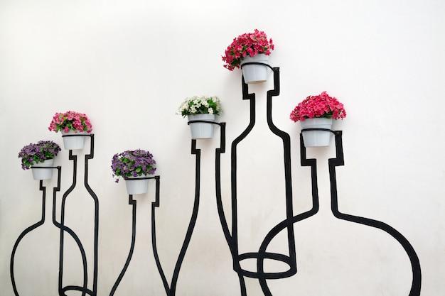 Patronen en texturen van witte cementmuur die met bloemen worden verfraaid.