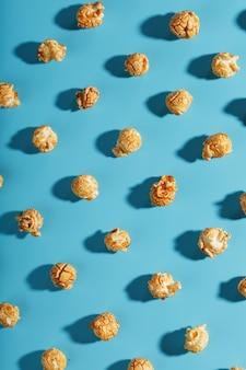 Patronen van karamelpopcorn op een blauwe achtergrond in de vorm van een patroon.