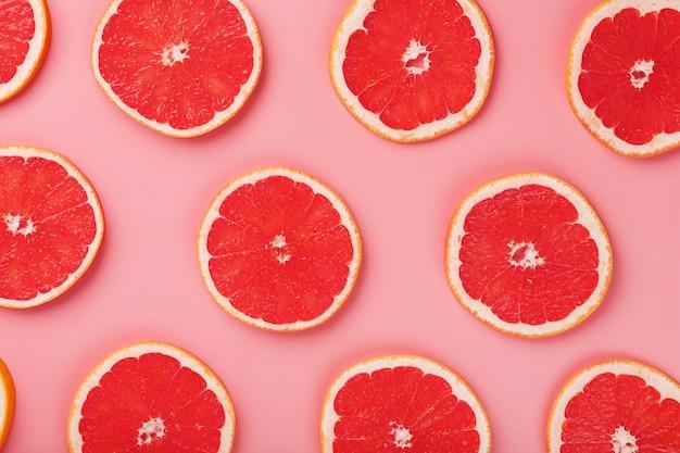 Patronen van plakjes sappige grapefruit op een roze achtergrond, een prachtig patroon. bovenaanzicht, volledig scherm