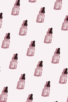 Patroon bovenaanzicht druppelflesje vitamine c-serum, cosmetische olie. creatieve cosmetica-patroonachtergrond in verticaal formaat voor verhalen