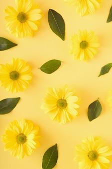 Patroon gemaakt van gele chrysant bloemen en groene bladeren op een gele achtergrond. monochromatisch natuur bloem concept.