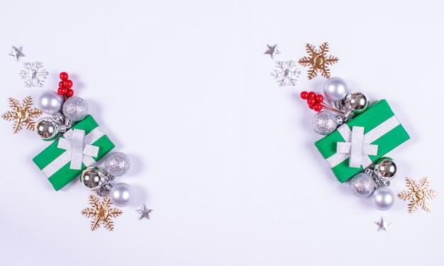 Patroon gemaakt van geschenkdozen, witte decoraties en sneeuwvlokken op witte achtergrond.