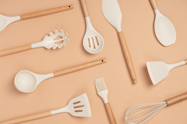 Patroon gemaakt van kookgerei set. siliconen keukengerei met houten handvat op beige achtergrond. bovenaanzicht plat lag.
