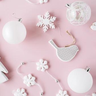 Patroon gemaakt van witte kerstversiering met glazen kerstballen, klatergoud, boog, elanden, vogel op roze achtergrond.