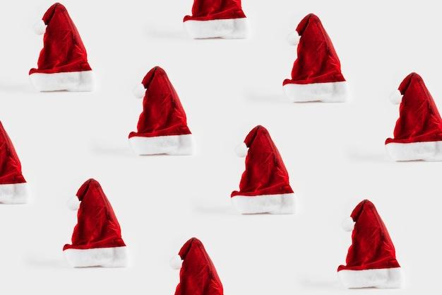 Patroon met kerst ornamenten inclusief santa's cap op witte achtergrond.