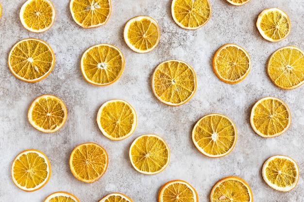 Patroon met plakjes gedroogde sinaasappel voedsel achtergrond bovenaanzicht plat leggen