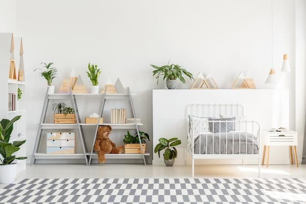 Patroon tapijt en planten in lichte tiener slaapkamer interieur met grijs bed. echte foto