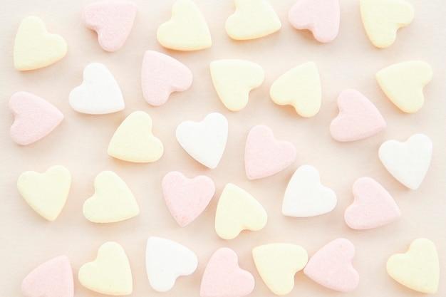Patroon van geel roze en witte snoep hartjes op een beige achtergrond.