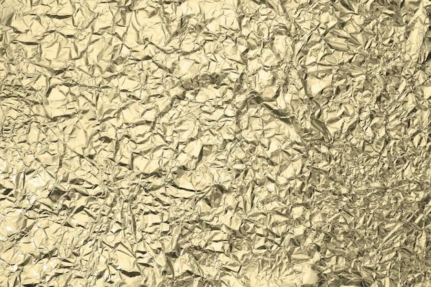 Patroon van gerimpeld gouden aluminiumfoliedocument die als achtergrond gebruiken