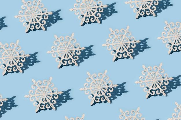 Patroon van kerstboomdecoratie in de vorm van sneeuwvlokken op een blauwe achtergrond
