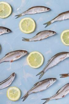 Patroon van kleine vis met schijfjes citroen op een blauw oppervlak, bovenaanzicht, verticale oriëntatie