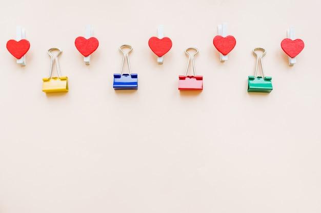 Patroon van kleurrijke bindmiddelklemmen en rode harten op pastelkleurdocument achtergrond