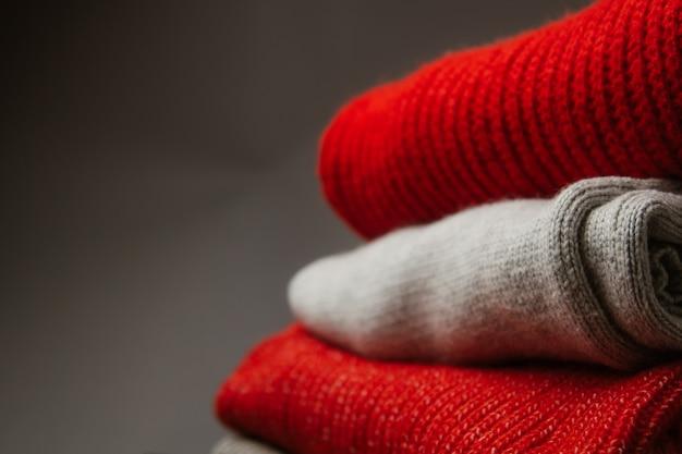 Patroon van kleurrijke gebreide sweatersclose-up. handgemaakt product van merinowol. een stapel gevouwen kleding met bloemen.