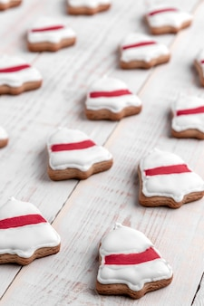 Patroon van koekjes vormige belring met rood glazuur op een witte houten achtergrond