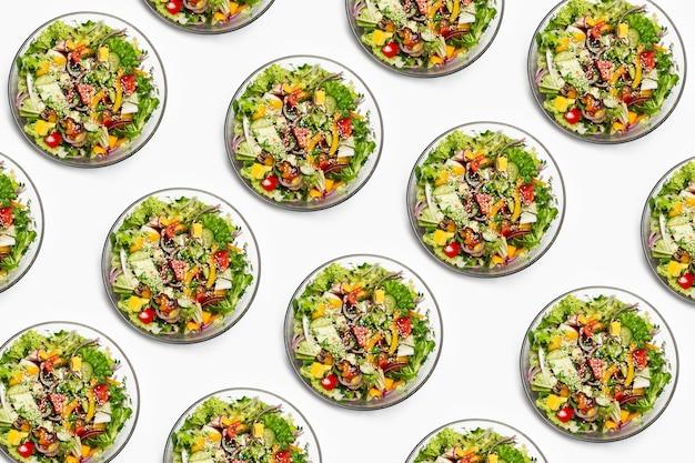 Patroon van kom met groene salade op witte achtergrond.
