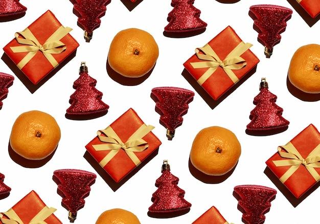 Patroon van mandarijnen glanzend rood speelgoed in de vorm van een kerstboom en een cadeau