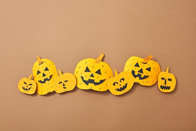 Patroon van papieren handwerkpompoenen met enge gezichten op een bruine achtergrond met kopieerruimte. samenstelling voor halloween. plat leggen