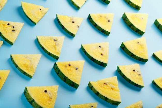 Patroon van plakjes verse plakjes rode en gele watermeloen op een blauw. bovenaanzicht