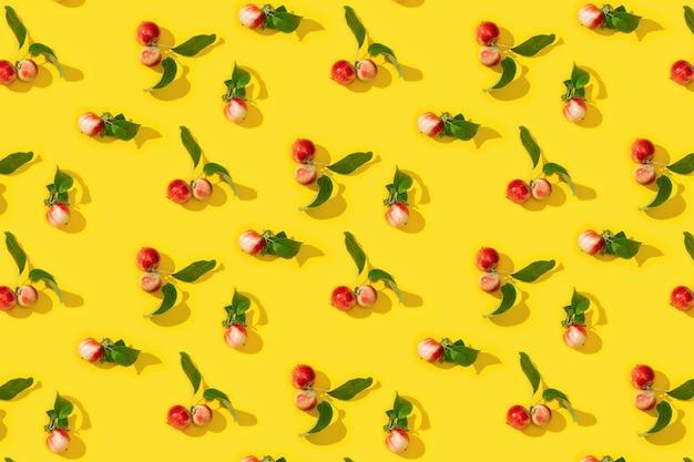 Patroon van rijpe kleine rode appels en groene bladeren op geel