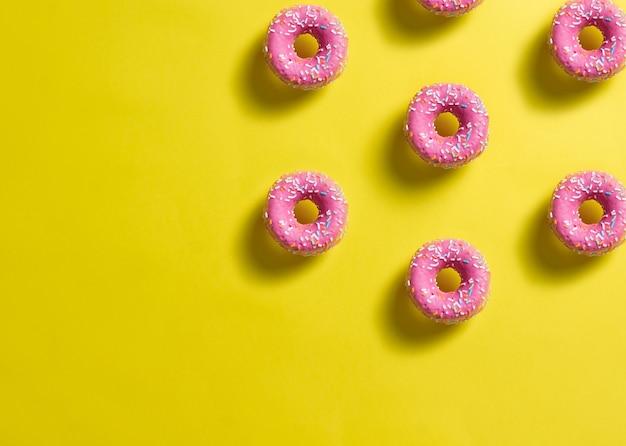 Patroon van roze donuts versierd met gekleurde confetti met schaduw op citroen gele achtergrond