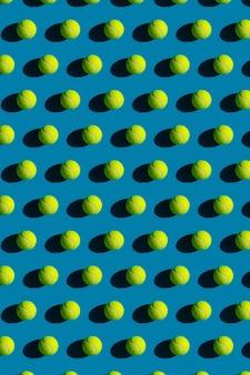 Patroon van tennisballen met sterke schaduwen op blauw