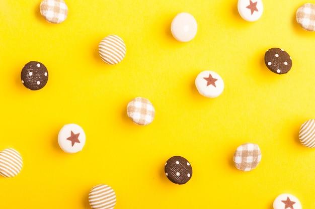 Patroon van textielknopen op gele achtergrond