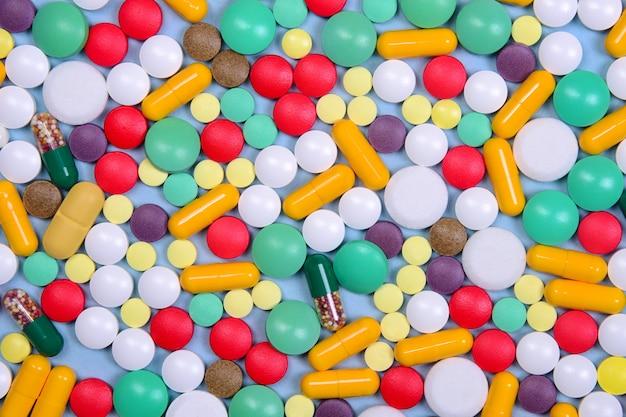 Patroon van veel gekleurde pillen, capsules en vitamines willekeurig verspreid.