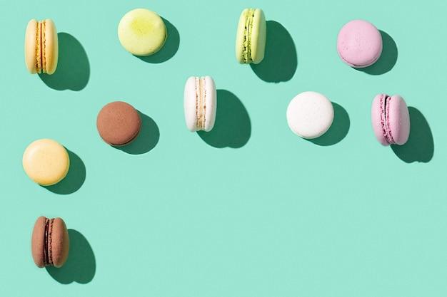Patroon van verschillende cakemakarons op helder blauwgroen