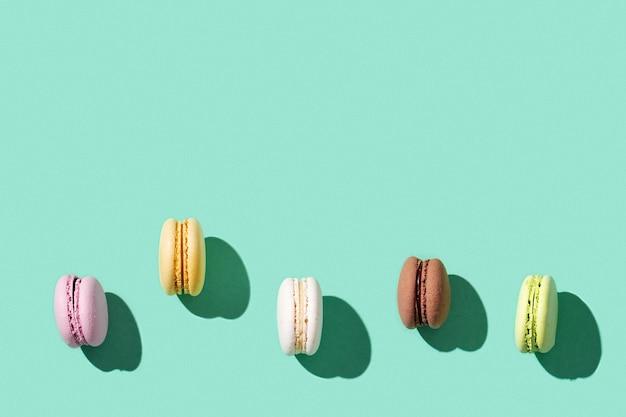 Patroon van verschillende cakemakarons op heldere blauwgroene kleur, multi gekleurde franse koekjesmacarons.
