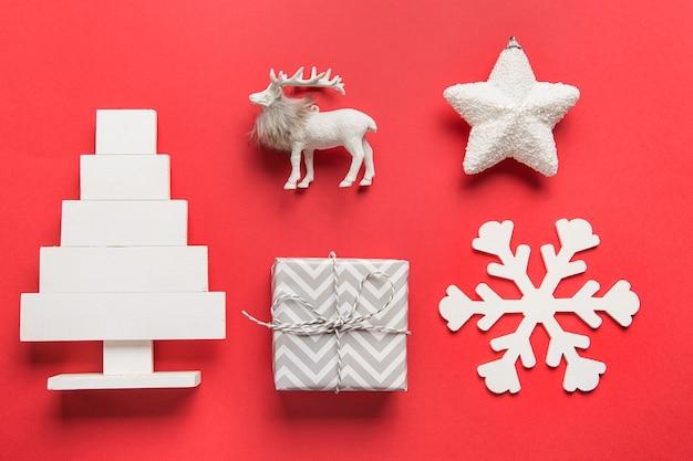 Patroon van witte kerstversiering, cadeau, alternatieve houten kerstboom, cadeau, ster, rendier, sneeuwvlok op rode ruimte